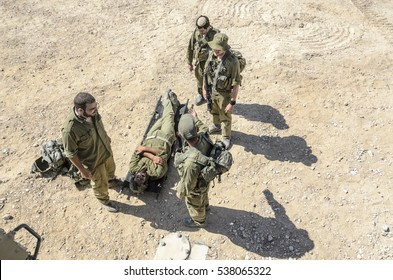 "MILITARY TRAINING ZONE, ISRAEL - JUNE 15, 2015: Israeli army infantry ""wounded"" soldier is laying down on a stretcher while fellow warriors are attending to him. Medical military combat training."