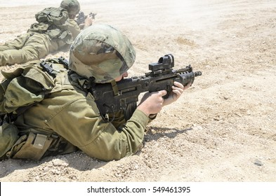 MILITARY TRAINING ZONE, ISRAEL - JUNE 17, 2015: Israeli army combat soldier firing at terror targets. Infantry troops shooting during military training in the desert. Soldiers aiming at enemy targets.