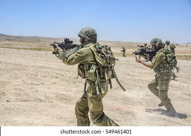 MILITARY TRAINING ZONE, ISRAEL - JUNE 17, 2015: Israeli army combat soldiers firing while charging on terror targets. Infantry troops storming & shooting during military training in the desert.