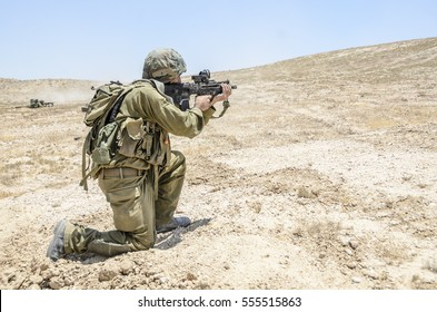 MILITARY TRAINING ZONE, ISRAEL - JUNE 17, 2015: Side view of Israeli army soldier crouching. Soldier firing an assault rifle during military training in the desert. Infantry soldier shooting weapon.