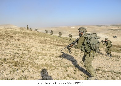 MILITARY TRAINING ZONE, ISRAEL - JUNE 17, 2015: Squad of Israeli army soldiers charging enemy targets. Special forces infantry troops shooting while running during army training in the desert.