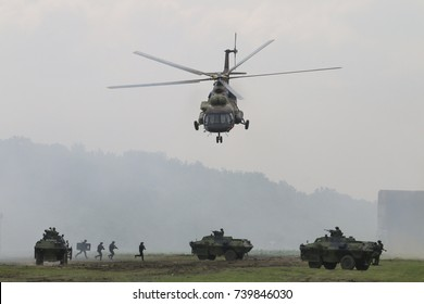 Military transport helicopter Mi 17 and armored vehicle attaking