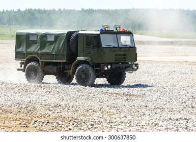 The military vehicle goes on the dusty road