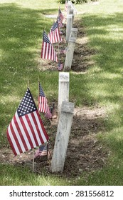 Military Veteran cemetery tombstones view with United States of America red, white and blue flags.