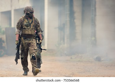 Military war conflict soldiers - Special forces soldier man hold Machine gun on a war field. Military equipment NATO soldiers