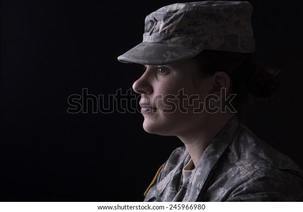 Military woman close up portrait, studio low key