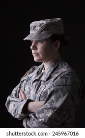Military woman fold her arms, studio low key