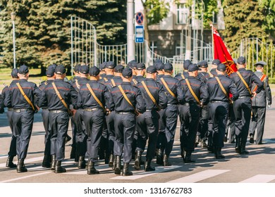 Militia squad in uniform with weapons marching in formation along a city street in Gomel on Victory Day on May 9