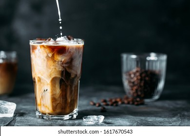 Milk Being Poured Into Iced Coffee on a dark table