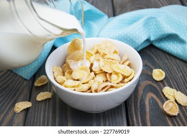 milk being poured over a bowl full of  cereal