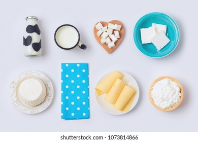 Milk bottle, cheese and dairy products on white background. View from above. Flat lay