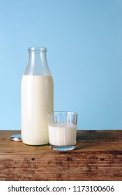 Milk bottle and glass with fresh milk, blue background
