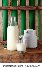 Milk bottle, glass with milk and milk jug, wooden fence