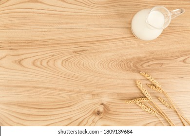 milk bottle and wheat ears on wooden background