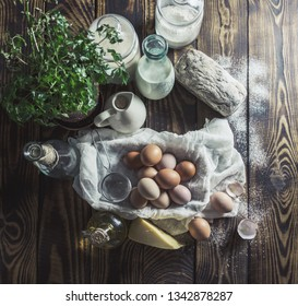Milk, bread and eggs in a basket on a rustic boards, top view
