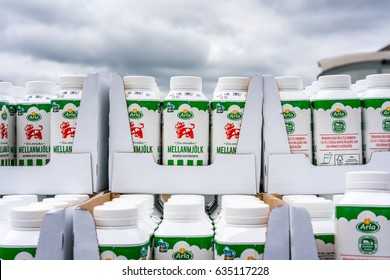 Milk cartons stacked outdoors.  Vallentuna, Sweden - May 06, 2017: Close up of many green milk cartons stacked in rows outdoors from Swedish milk manufacturer Arla, Labeled with their red cow logo.