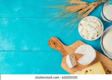 Milk and cheese, dairy products on wooden blue background. Jewish holiday Shavuot concept. View from above
