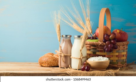 Milk, chocolate milk bottles and basket with fruits on wooden table. Jewish holiday shavuot concept.
