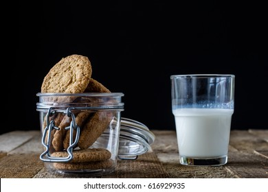 Milk and chocolate cookies on an old wooden table, black background