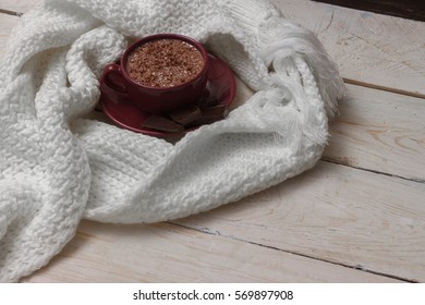Milk chocolate in a cup on a saucer against a background of a scarf and a wooden background.