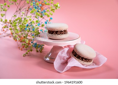Milk chocolate ganache refined with coconut puree and a core of coconut. The macaron shells are naturally colored with a touch of cocoa powder. Pyramid of macarons on a pink cake bowl. Pink background