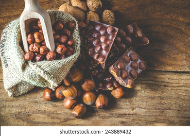 milk chocolate with hazelnuts and walnuts in a sack on a wooden background