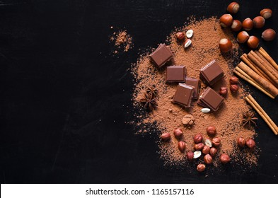 Milk chocolate with nuts and cocoa powder on dark background. Top view