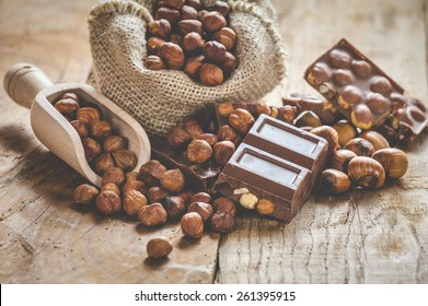 Milk chocolate with nuts on a wooden spoon in a country style.