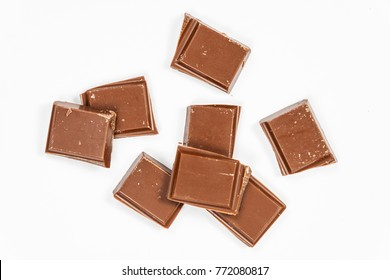 Milk chocolate pieces isolated on white background, top view