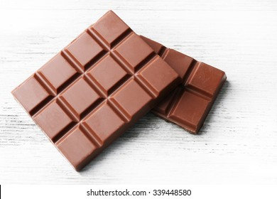 Milk chocolate pieces on color wooden background