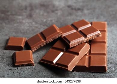Milk chocolate pieces on gray background