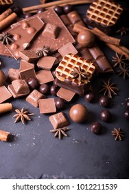 milk chokolate with whole hazelnuts and round candies and cookies on granite background/ cinnamon sticks, nuts, aroma spices