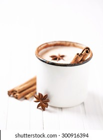 Milk with cinnamon and anise in rustic mug on white wooden table