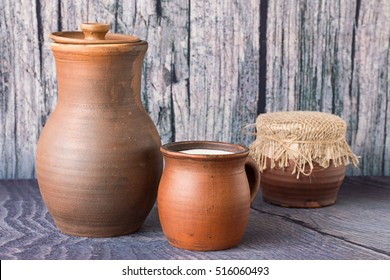 Milk in a clay mug and in jug, near the pot with sour cream, on the gray wooden background.