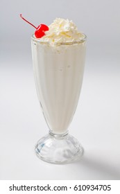 milk cocktail with a cherry in a tall glass. Isolated