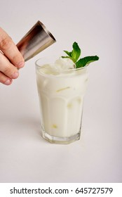 Milk or coconut coctail. White coctail. Hand dropping coffe inside. Pour coffe or syrup in coctail