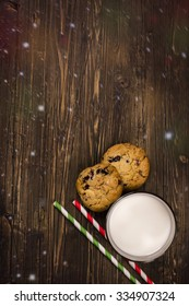 Milk and cookies for Santa Claus over wooden background. Xmas concept, magic greeting card. Toned image. Top view