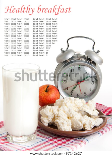 Milk, cottage cheese and alarm clock on the red napkin