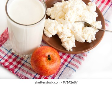 Milk, cottage cheese and apple on the red napkin
