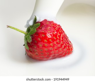 milk or cream poured on fresh red strawberry, close up