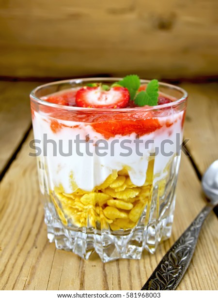 Milk dessert with strawberries, corn flakes and yogurt in a glass, a spoon on a background of wooden boards