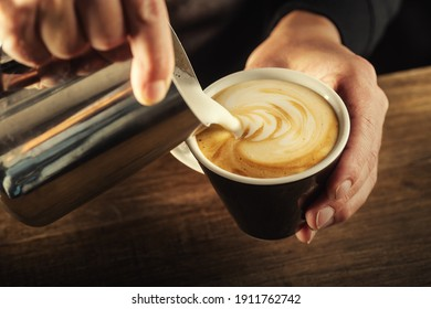 Milk foam poured into a cup to form a perfect cappuccino - coffee art.