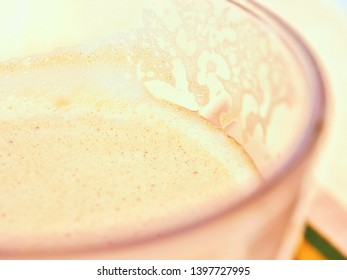 Milk froth of a milk coffee in a glass in close-up, very bright, very soft, also background, texture.