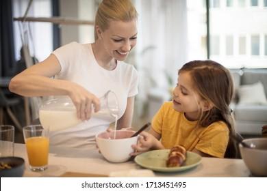 Milk is good for your bones. Mother preparing her daughter breakfast.