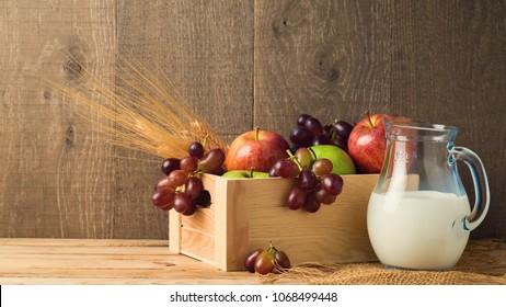 Milk jug and box with fruits on wooden table. Jewish holiday shavuot concept.