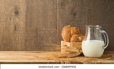 Milk jug and bread on wooden table. Jewish holiday Shavuot concept.