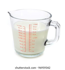 Milk in measuring cup on white background