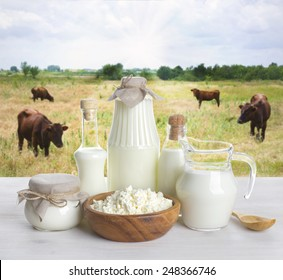 Milk on wooden table with cows on the background