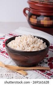 Milk porridge of crushed barley grains in a ceramic bowl