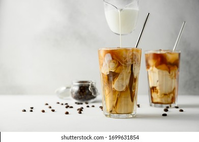 Milk is poured into coffee with ice on a light background. Two transparent glasses of refreshing iced coffee on a white table. Horizontal orientation, copy space.